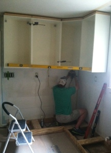 David installing the upper cabinets. Have to make sure they are level!